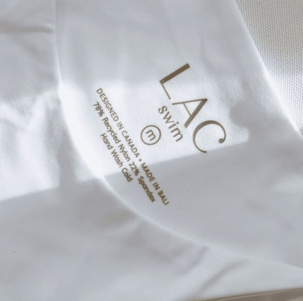 Close up of a LAC swimsuit bottom in white. The logo says LAC Swim and explains that it is designed in Canada and made in Bali.