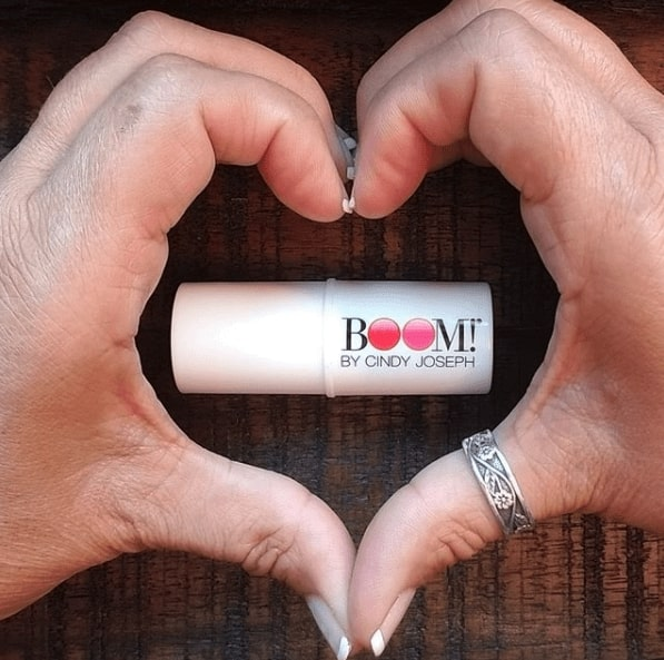 Close up of someone making a heart with their hands. In the middle is a lipstick that says BOOM! By Cindy Joseph