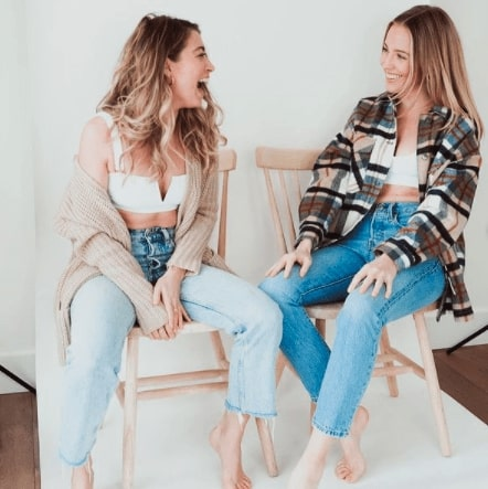 Founders of LAC Swim. Alex Bennett is sitting on the left and Paige Harris is sitting on the right. They are both wearing white LAC swim tops and light. blue jeans