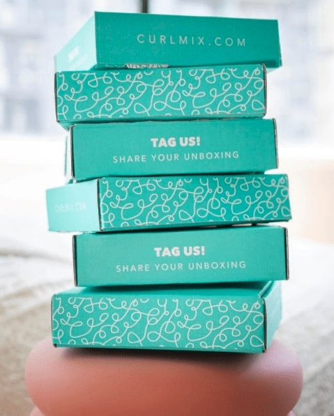 Stack of teal boxes from Curlmix that share the website domain and say _Tag us! Share your unboxing._