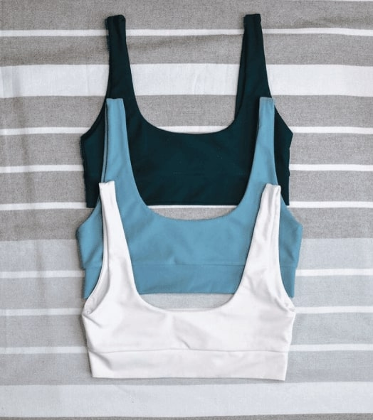 Three LAC Swim tops stacked on top of each other. One is dark green_ one is light blue_ and one is white. They are on top of a striped grey background