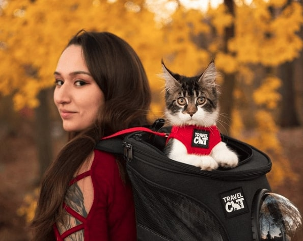 Woman with long brown hair in a red shirt wearing a black backpack. There is a white and grey cat popping its head out of the top of the backpack