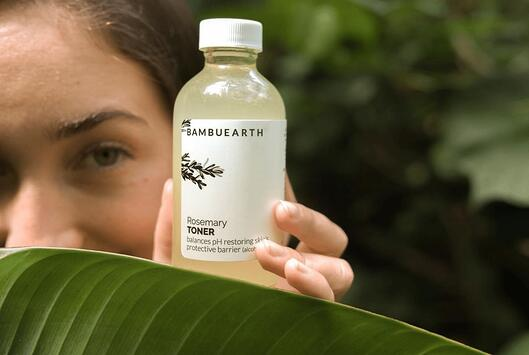 close up of a bottle of Bambu Earths rosemary toner. Behind the bottle is a woman looking at it. Theres a large leaf covering half her face and part of the bottle