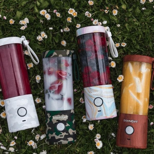 four blendjets sitting in the grass. Each has fruit or blended fruit inside